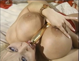Hot blonde in red dress and huge tits finger fucks her pussy on the bed