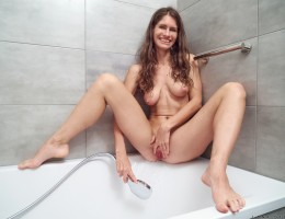 Ready to hop into the shower, cute sweetheart Lana Stotch starts stripping. Her underwear and bra are the last to hit the ground, leaving her nude and caressing her tight body. Stepping into the tub, she spreads her pussy lips and then points the shower s